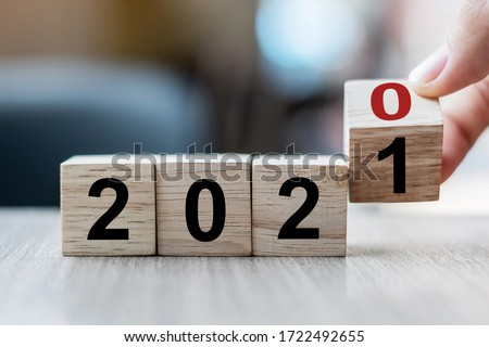 Businessman hand holding wooden cube with flip over block 2020 to 2021 Plans word on table background. Resolution, strategy, solution, goal, business and New Year holiday concepts