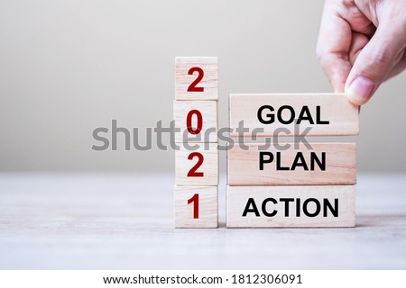 Photo of  Businessman hand holding wooden cube with text 2021 GOAL, PLAN and ACTION on table background. Resolution, strategy, solution, goal, business and New Year holiday concepts