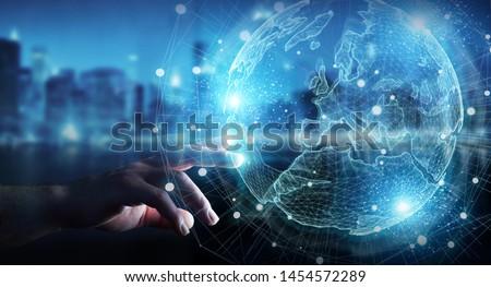 Businessman hand in dark using Europe map globe network hologram 3D rendering