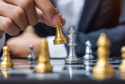 businessman hand moving gold Chess King figure and Checkmate opponent during chessboard competition. Strategy, Success, management, business planning, disruption and leadership concept