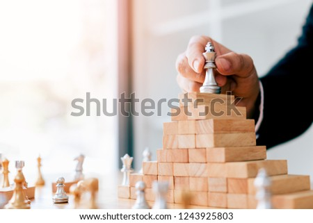 Businessman hand picking chess on top block wood about leadership concept.