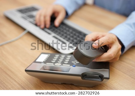 businessman hand picking up telephone receiver on business workplace