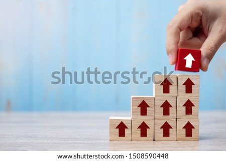 Businessman hand placing or pulling Red block with arrow and growth up arrow on table background. Business Growth, Improvement, strategy, Successful, success, winner and Mission complete Concepts