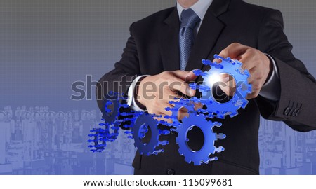 businessman hand point blue gear to success as concept