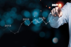 Businessman hand point drawing increase trend arrow and growing chart from 2020 to 2021 on black background. It is symbol of business investment growth concept.