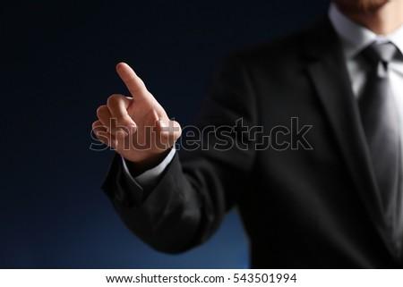 Businessman hand pointing, dark background #543501994