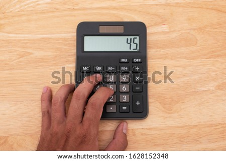 Businessman hand pressing on calculator for calculating numbers. Hand press button use calculator. Calculator with finger. Fingers pressing the buttons of calculator.
