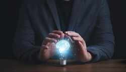 Businessman hand protecting with lightbulb with virtual brain glowing , patent and creative idea innovation concept.