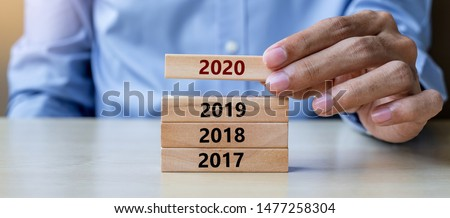 Businessman hand pulling 2020 wooden building blocks on table background. Business planning, Risk Management, Resolution, strategy, solution, goal, New Year New You and happy holiday concepts