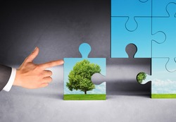 Businessman hand pushing puzzle piece with nature picture