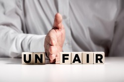 Businessman hand puts away the first two letters from the word unfair and transforms it into fair. Justice and fairness in business concept.