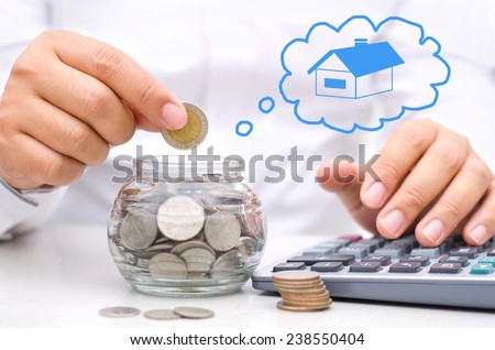 businessman hand putting money coins into glass piggy bank for buy home