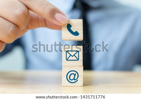 Businessman hand putting wooden block cube symbol telephone, email, address. Website page contact us or e-mail marketing concept #1431711776