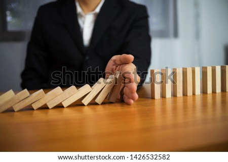 Businessman hand stops domino continuous overturned meaning that hindered business failure. Stop over this business failure concept.