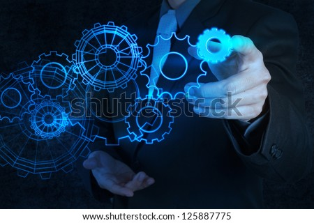 businessman hand touch blue gear to success concept
