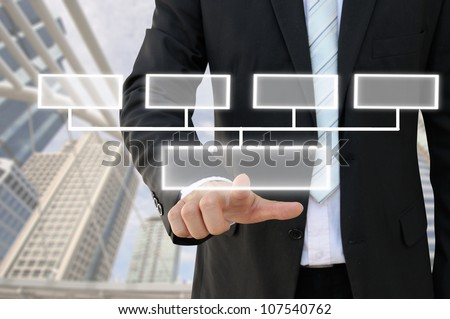 Businessman hand touch screen button of 4 choices blank chart with building background