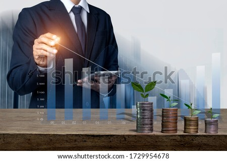 Businessman hand  touch screen on   virtual financial chart and stack of coins on wood bar, Business financial concept.