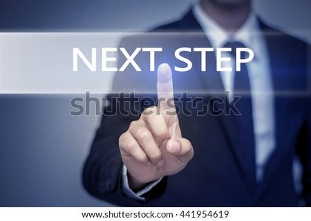 Businessman hand touching NEXT STEP button on virtual screen