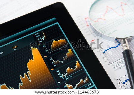 Businessman hand touching screen of tablet pc with market graph