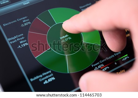Businessman hand touching screen of tablet pc with market graph - stock photo