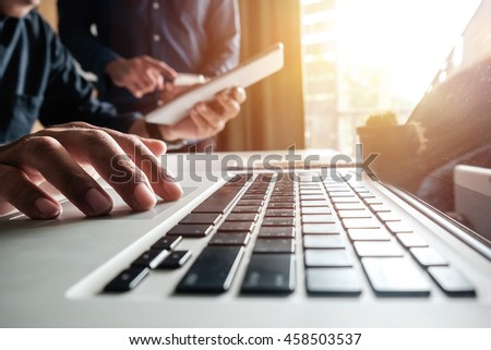 Businessman hand using laptop and tablet with social network diagram and two colleagues discussing data on desk as concept in morning light. - Shutterstock ID 458503537