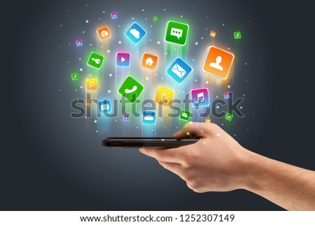 Businessman hand using phone with flying application icons around #1252307149