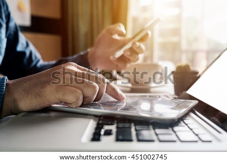 Businessman hand using smart phone, laptop and tablet with social network diagram on desk as concept in morning light.