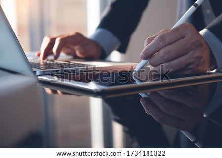 Businessman hand using stylus pen signing contract on digital tablet while working on laptop computer in modern office, electronic signature. Business man taking note on touchpad, business concept Foto stock ©