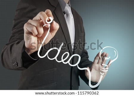 businessman hand with a pen drawing light bulb