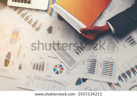 Businessman hand with modern gray suit open brown envelope for analysis report paper on table in office with computer laptop, Business executive going through paperwork concept. Top view & copy space