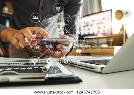 Businessman hand working digital marketing media in virtual screen with mobile phone and modern compute with VR icon diagram at office in morning light  #1243741705