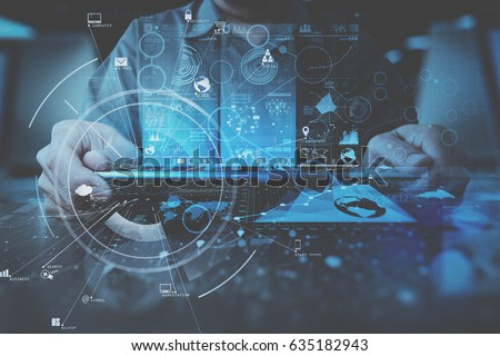businessman hand working with modern digital tablet computer in modern office with virtual icon diagram #635182943