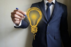 businessman hand writing light bulb, business idea concept