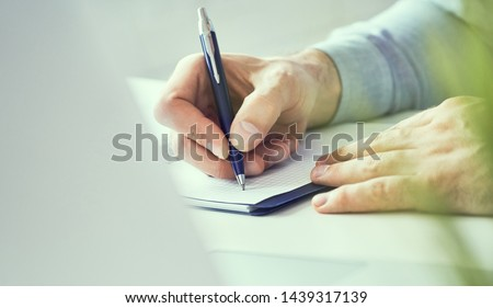 Businessman hand writing note on a notebook close-up. Business man working at office desk. Close up of empty notebook on a blackboard with office supplies.