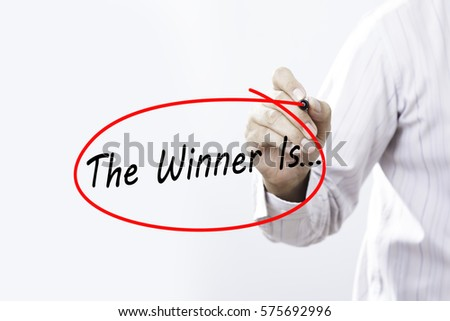 Businessman Hand Writing The Winner Is... with a marker over transparent board,  Business concept. #575692996