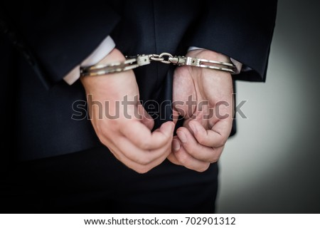 Businessman handcuffed arrested for corruption, money laundering, tax evasion, antitrust violations, bank fraud, Bribery, blackmail, counterfeiting, Embezzlement, forgery and insider trading  #702901312