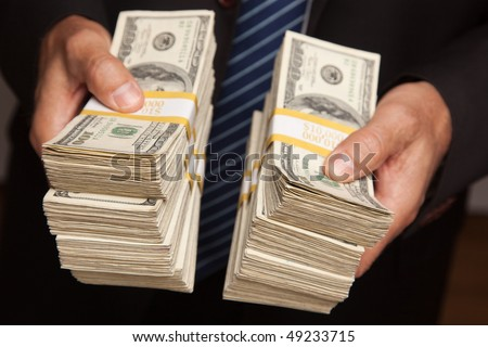 Businessman Handing Over Stacks of Hundred Dollar Bills.