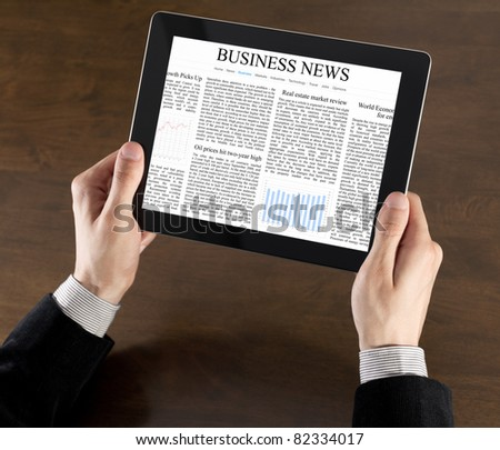 Businessman hands are holding the touch screen device with business news on screen