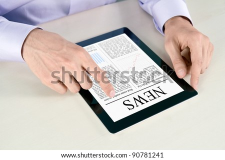 Businessman hands are pointing on contemporary digital tablet pc with latest news lying on table.