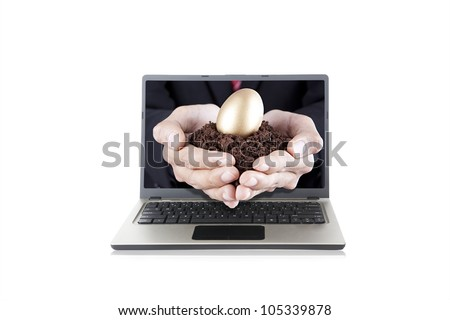 Businessman hands holding golden egg with soil on the palm out from laptop