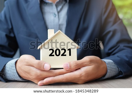 Businessman hands holding wooden House model with 2021 New Year text. Property insurance and real estate concepts