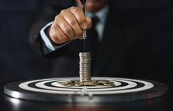 Businessman hands in black suite sitting and holding black dart put to centre of target board with stacking coin on vintage table meaning of investment and achievement goal. Plann and strategy concept