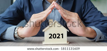 Businessman hands over wooden House model with 2021 New Year text. Property insurance and real estate concepts