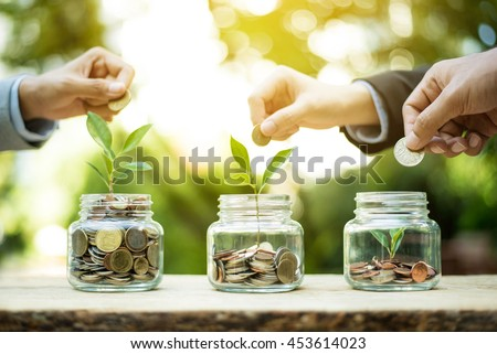Businessman hands putting money (coin) into the glass jar - savings and investment  concept