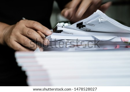 Businessman hands searching unfinished documents stacks of paper files on office desk for report papers, piles of sheet achieves with clips on table, Document is written, drawn,presented. #1478528027