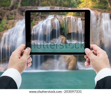 Businessman hands tablet taking pictures Waterfall deep forest  at Erawan waterfall National Park Kanchanaburi of Thailand