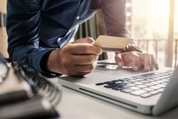 Businessman hands using smartphone laptop and holding credit card with social media as Online shopping concept in morning light.vintage effect