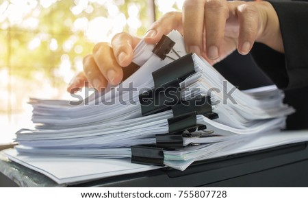 Businessman hands working in Stacks of document paper files for searching information on work desk office, business report papers, piles of unfinished documents achieves with clips.  #755807728