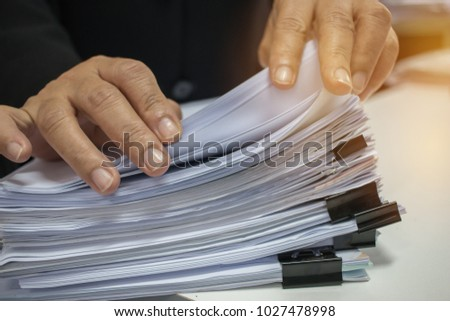 Businessman hands working in Stacks of paper files for searching information on work desk office, business report papers,piles of unfinished documents achieves with clips indoor,Business concept #1027478998