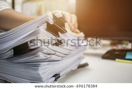 Businessman hands working in Stacks of paper files for searching information on work desk office, business report papers,piles of unfinished documents achieves with clips indoor,Business concept #696178384
